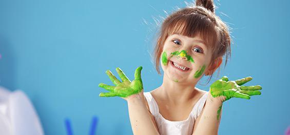 Une jeune fille, les mains dans la peinture verte