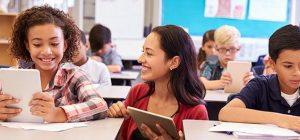 Enseignante souriante à côté de jeunes élèves en classe