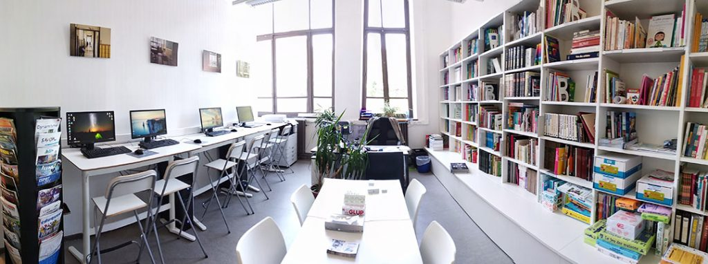 Photo intérieure de la bibliothèque de Jonfosse, avec table, livres et PC à disposition